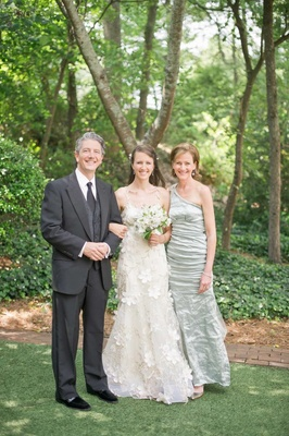 Bride with father and mother in light green dress