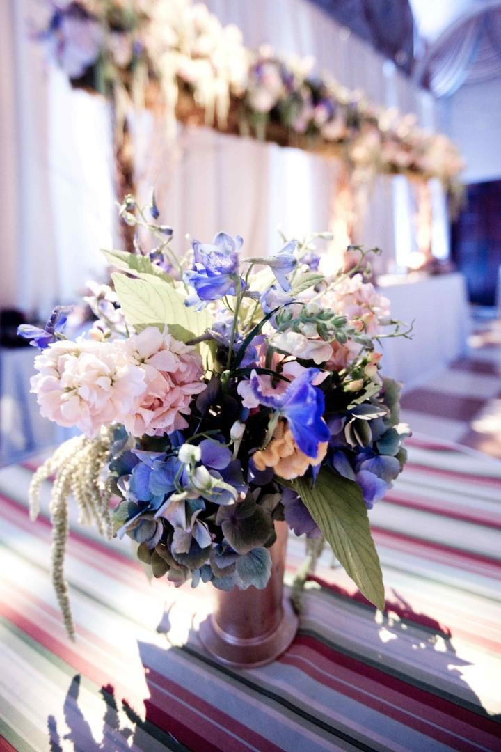 Pink, purple, and blue flowers in metallic vase on striped table
