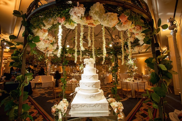 White six layer wedding cake under wrought iron flower chandelier