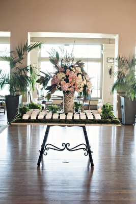 wedding escort cards on table covered in moss, flower arrangement in birch tree trunk