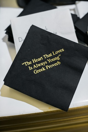 black cocktail napkin with gold printed greek proverb