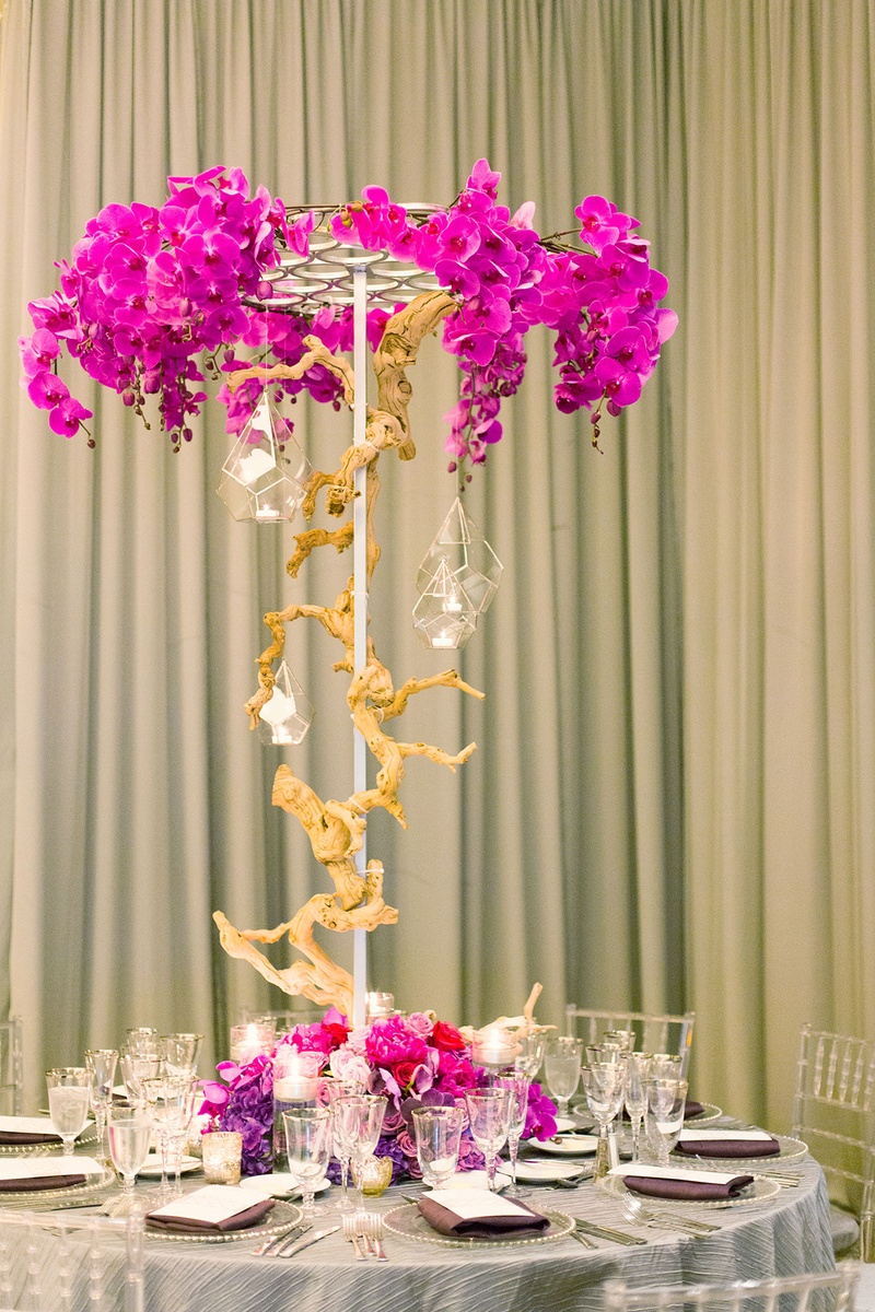 pink and purple orchid floral centerpiece wood branch glass vase lights arrangements