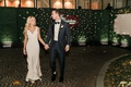bride and groom walking away from wedding neon sign v neck dress long blonde hair