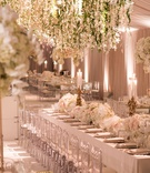 Wedding reception blush tent long table clear chairs white flowers gold candleholders greenery over