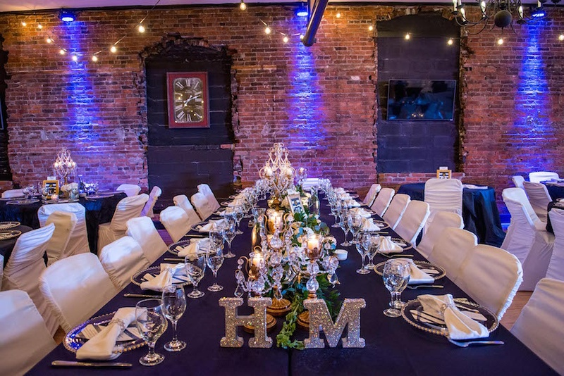 Wedding reception venue with brick wall and blue lighting