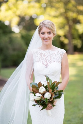 Bride wearing lace wedding dress with sweetheart neckline high lace neck illusion magnolia bouquet