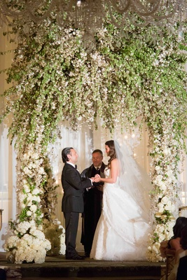 towering canopy wedding arch with lush greenery and white florals