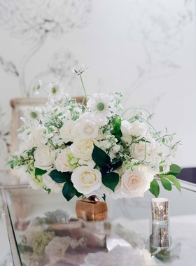 mirror table copper vessel filled with green leaves, white roses, blush roses, white garden roses
