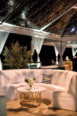 wedding reception tent twinkle lights white sofa settee pillow marble coffee table