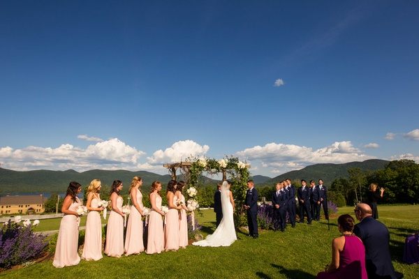 couple marrying wedding party wooden arch outdoors vermont mountains