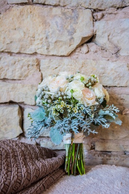 White ranunculus, white rose, and dusty miller bouquet