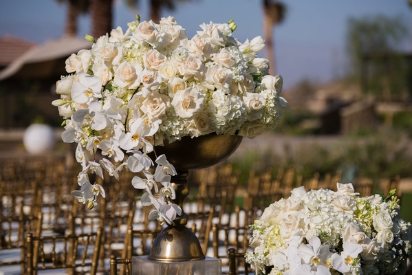 Gold ceremony chairs with gold urns on riser with white hydrangea, rose, tulip, and orchid flowers