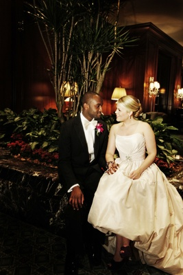 Bride in a strapless Amsale gown holds hands with groom in a black tuxedo