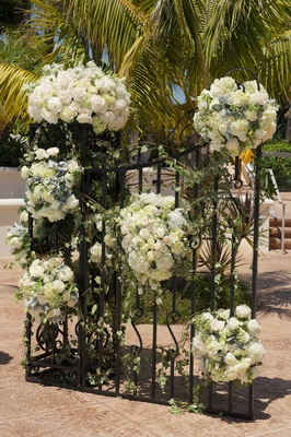 Wrought iron gate with white flowers and greenery