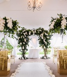 wedding ceremony tent white gold greenery color palette orchid leaves trees gold chairs