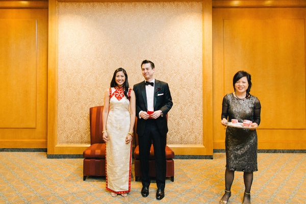 Chinese bride in a white Qipao with gold embroidery and red trim with groom in black tuxedo
