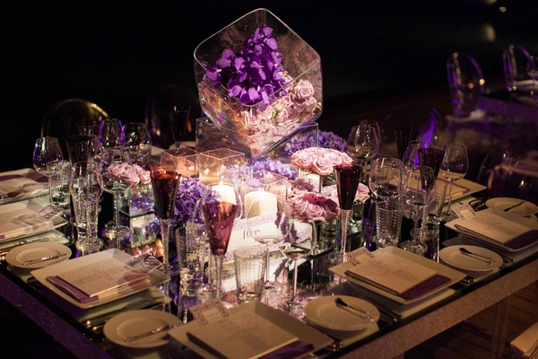 Purple flowers and glassware on mirror reception table