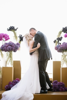 Wedding ceremony kiss bride and groom gold stage altar with purple flowers hydrangea calla lily