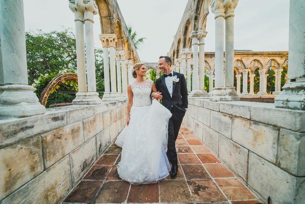 bride and groom walking down column path at the ocean club four seasons bahamas