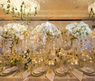 tall and low floral arrangements with white roses and orchids