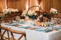 ocean inspired wedding reception with wood bud vases, succulents, blue charger, gold flatware