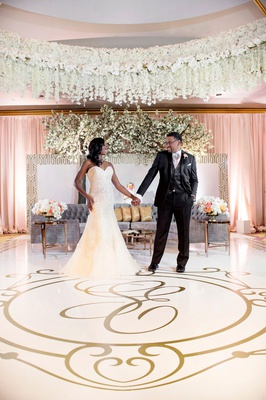 Bride & Groom Hold Hands in reception ballroom gold monogram dance floor grey tufted sofa lounge