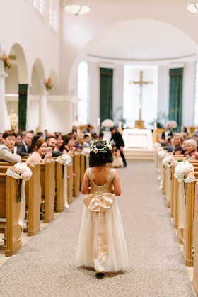 Flower girl with short haircut and flower crown scoop back dress with large bow on back walking down