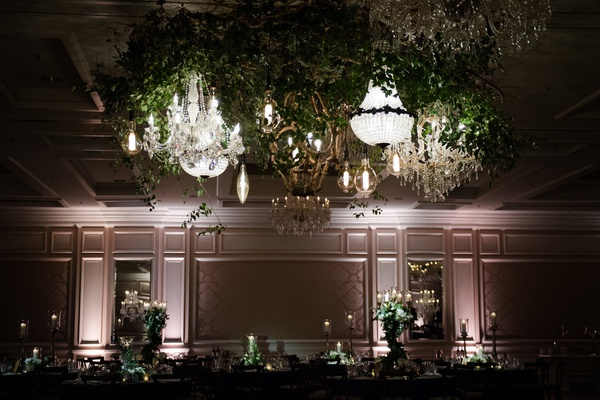 greenery above dance floor with several chandeliers at wedding reception