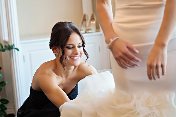 smiling bridesmaid in black dress helps bride into her mermaid style wedding dress