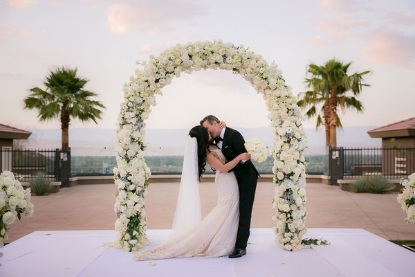 Outdoor wedding ceremony bride and groom kissing galia lahav dress white flowers palm trees