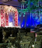 Wedding ceremony with green chairs and pink flower chuppah