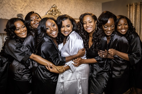 bride in white satin robe, bridesmaids in black satin robes, bride and bridesmaids hug while getting