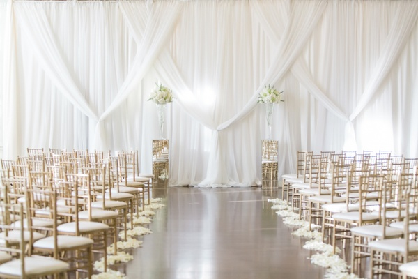 Aisle with flower petals and white backdrop at Biltmore Ballrooms in Atlanta gold chairs