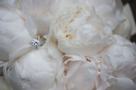 Wedding ring solitaire diamond engagement ring pave band on white peony bouquet