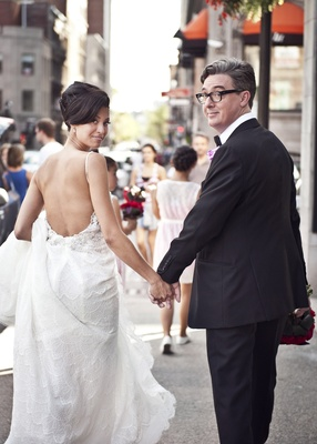bride in pnina tornai lace wedding dress open back, groom with glasses, look back while walking