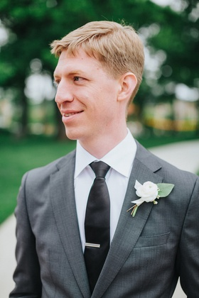 groom in grey suit, black tie with silver tie bar, white flower and green leaf boutonniere