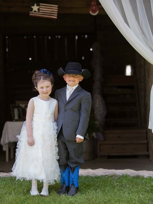 Flower girl in tank ruffle dress with ring bearer in grey suit with cowboy boots and hat