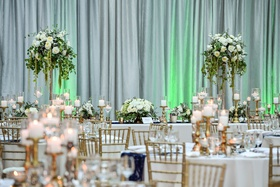 wedding reception drapery green lighting white greenery centerpiece gold chair candlesticks navy