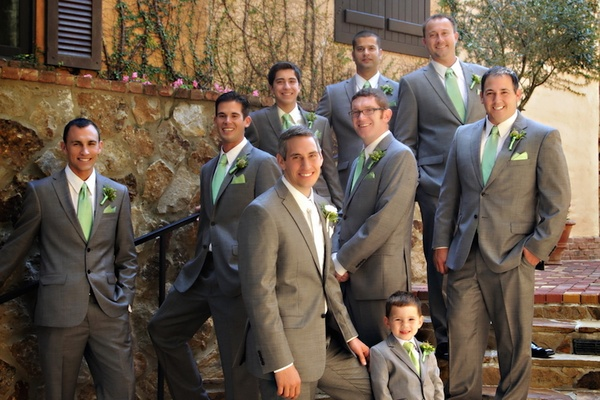 Men in gray tuxedos with green ties and boutonnieres