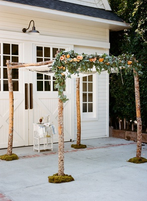 Wedding ceremony arbor chuppah branches with greenery and peach orange rose flowers