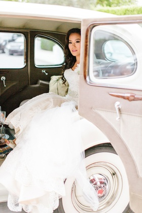 Bride in trumpet wedding dress getting into or out of a vintage packard car at ceremony