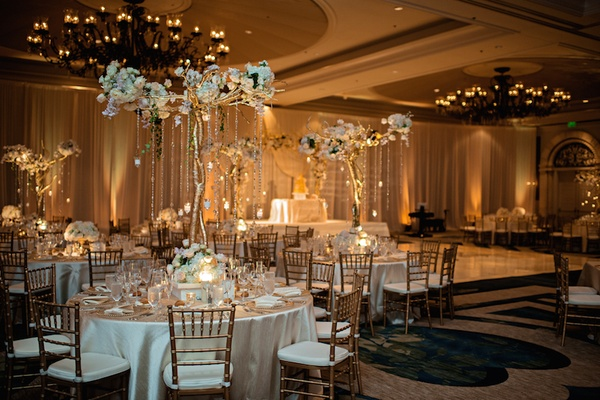 Candlelit reception hall with gilt chairs and ivory linens