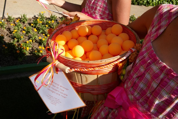 Flower girls in plaid dresses with orange ping pong balls