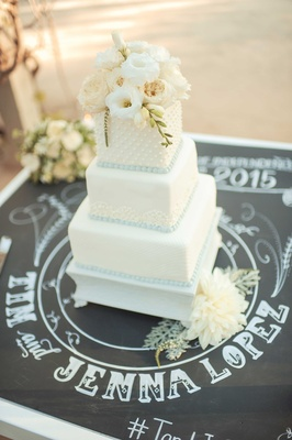 Tim Lopez and Jenna Reeves wedding cake rustic reception white square tiers fresh flowers