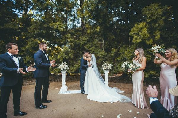 groom in the black tux suit kisses bride in stella york gown as bridesmaids and groomsmen applaud