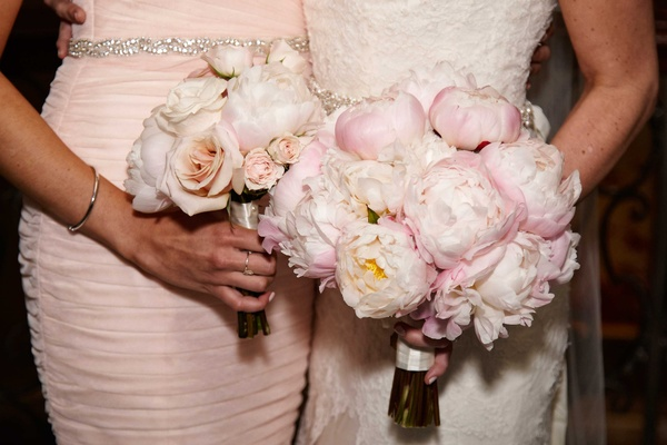 Bride with light pink peony wedding bouquet and bridesmaid with light pink rose bouquet