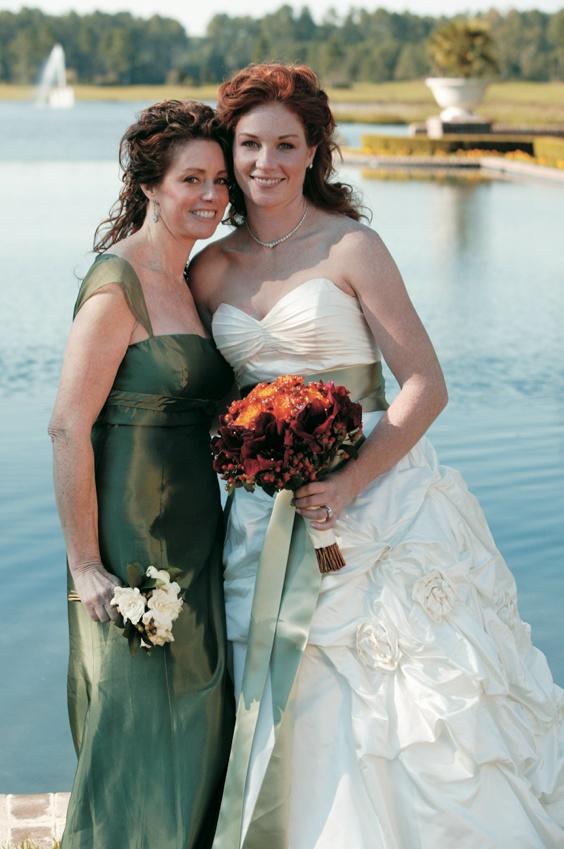 Bride in ball gown with sage sash in front of lake with mother of bride in green dress