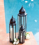 Black panel lantern filled with tall candles next to pool