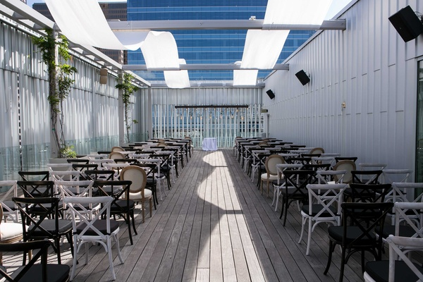 a semi-open ceremony space on rooftop with white concept foliage alternating black and white chairs