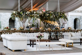 wedding reception head table flower chandelier lounge areas chesterfield sofas tufted wood tables